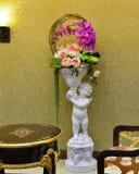 Cesta de la flor y escultura del niño Fotografía de archivo libre de regalías