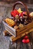 Cesta de la Navidad con las decoraciones del árbol del Nuevo-año y los conos del pino Fotografía de archivo libre de regalías