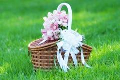 Cesta de la paja con las flores en una hierba verde Fotos de archivo