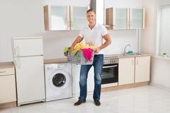 Cesta de lavadero del hombre que lleva en sitio de la cocina Foto de archivo libre de regalías