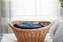 Cesta de lavanderia com as calças de brim ordenadamente dobradas imagem de stock royalty free