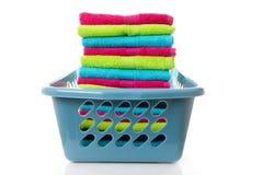 Cesta de lavanderia enchida com as toalhas dobradas coloridas Fotografia de Stock