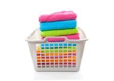 Cesta de lavanderia enchida com as toalhas dobradas coloridas Imagens de Stock Royalty Free