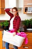 Cesta de lavanderia levando da jovem mulher cansado na cozinha imagens de stock