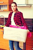 Cesta de lavanderia levando da jovem mulher feliz na cozinha fotografia de stock royalty free