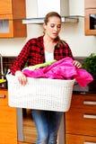 Cesta de lavanderia levando da jovem mulher feliz na cozinha foto de stock