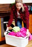 Cesta de lavanderia levando da mulher cansado na cozinha fotografia de stock