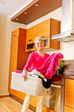 Cesta de lavanderia levando da mulher superior na cozinha imagem de stock