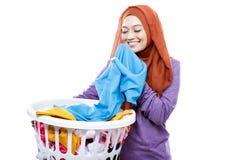 Cesta de lavanderia levando vestindo do hijab da jovem mulher ao cheirar Fotografia de Stock