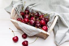 Cesta de madera de cerezas frescas en una servilleta gris del algodón en el fondo blanco imagen de archivo
