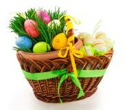 Cesta de madera de mimbre con los huevos de Pascua y la hierba fresca Imagen de archivo