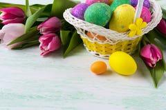 Cesta de mimbre amarilla de Pascua con los huevos multicolores Fotografía de archivo libre de regalías