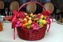 Cesta de mimbre con las frutas y las flores de la mezcla Imagen de archivo libre de regalías