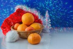 Cesta de mimbre con las naranjas y las mandarinas en el fondo de los fuegos artificiales Imágenes de archivo libres de regalías