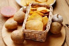 Cesta de mimbre con las patatas fritas, la patata y la salsa Fotografía de archivo