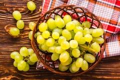 Cesta de mimbre con las uvas y servilleta en la tabla de madera Fotografía de archivo