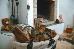 Cesta de mimbre con leña cerca de la chimenea imágenes de archivo libres de regalías