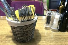 Cesta de mimbre con los cubiertos y servilletas amarillas en una tabla de madera en un restaurante foto de archivo