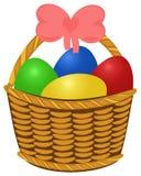 Cesta de mimbre con los huevos de Pascua coloreados Fotografía de archivo libre de regalías