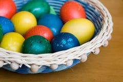 Cesta de mimbre con los huevos de Pascua coloreados hechos a mano Fotos de archivo libres de regalías