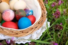 Cesta de mimbre con los huevos de Pascua coloridos Fotografía de archivo