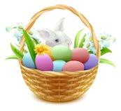 Cesta de mimbre con los huevos, las flores y el conejito de Pascua