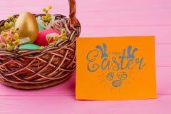 Cesta de mimbre con los huevos de Pascua coloridos Imagen de archivo