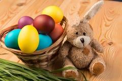 cesta de mimbre con los huevos y el conejo de Pascua en un de madera Imagen de archivo