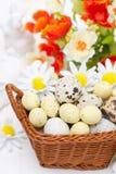 Cesta de mimbre con los huevos y las flores de Pascua Imagen de archivo