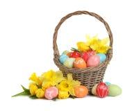 Cesta de mimbre con los huevos y las flores pintados de Pascua fotos de archivo libres de regalías