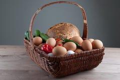 Cesta de mimbre con los huevos y las verduras Fotografía de archivo