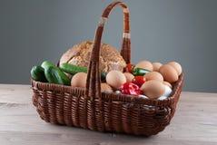 Cesta de mimbre con los huevos y las verduras Imagen de archivo
