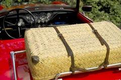 Cesta de mimbre de la comida campestre en un coche de deportes del rojo Fotos de archivo libres de regalías
