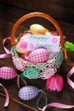 Cesta de mimbre de Pascua con los huevos y la tarjeta de felicitación Foto de archivo libre de regalías