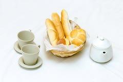 Cesta de mimbre del desayuno del almuerzo con el pequeños baguette y buñuelo y tetera franceses en el fondo blanco Imagen de archivo