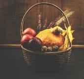Cesta de mimbre del otoño con la calabaza, las manzanas, las hojas y las nueces en fondo negro y de madera Fotografía de archivo