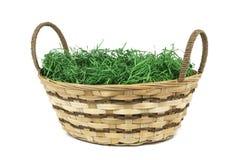 Cesta de mimbre de Pascua con la hierba verde en el fondo blanco aislado imágenes de archivo libres de regalías
