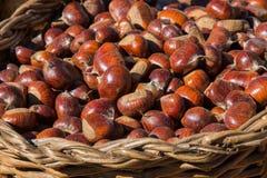 Cesta de mimbre por completo de castaña orgánica dulce en el mercado del país Imagen de archivo libre de regalías