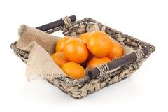Cesta de mimbre por completo de frutas anaranjadas frescas Foto de archivo