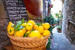 Cesta de mimbre por completo de limones en la calle italiana foto de archivo