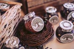 Cesta de mimbre y tarros de cristal con el relleno Elementos decorativos del evento solemne Foto de archivo libre de regalías