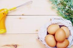 Cesta de ovos de Brown com o batedor de ovos no fundo de madeira Fotos de Stock Royalty Free