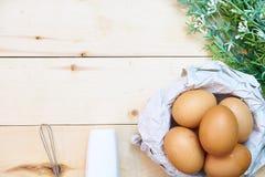 Cesta de ovos de Brown com o batedor de ovos no fundo de madeira Fotografia de Stock