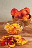 Cesta de pêssegos inteiros, orgânicos, locais e de uma bacia de pêssegos cortados Imagens de Stock Royalty Free