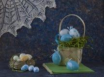 Cesta de Pascua con los huevos de Pascua coloreados en la tabla de piedra oscura imagen de archivo