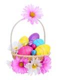 Cesta de Pascua con los huevos coloridos y las flores de la manzanilla aislados Fotografía de archivo
