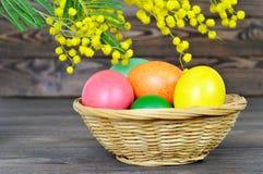 Cesta de Pascua con los huevos de Pascua coloridos Fotografía de archivo