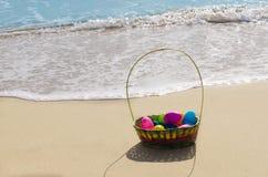 Cesta de Pascua con los huevos en la playa Foto de archivo