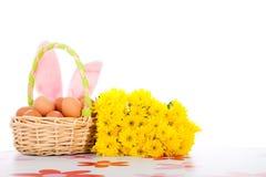 Cesta de Pascua con los huevos, las flores y los oídos del conejito Foto de archivo