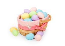 Cesta de Pascua con los huevos plásticos coloreados en colores pastel Imagen de archivo